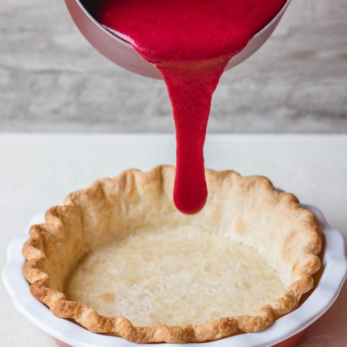 Pie crust filled with cranberry custard before baking