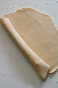 pie dough wrapped around the rolling pin