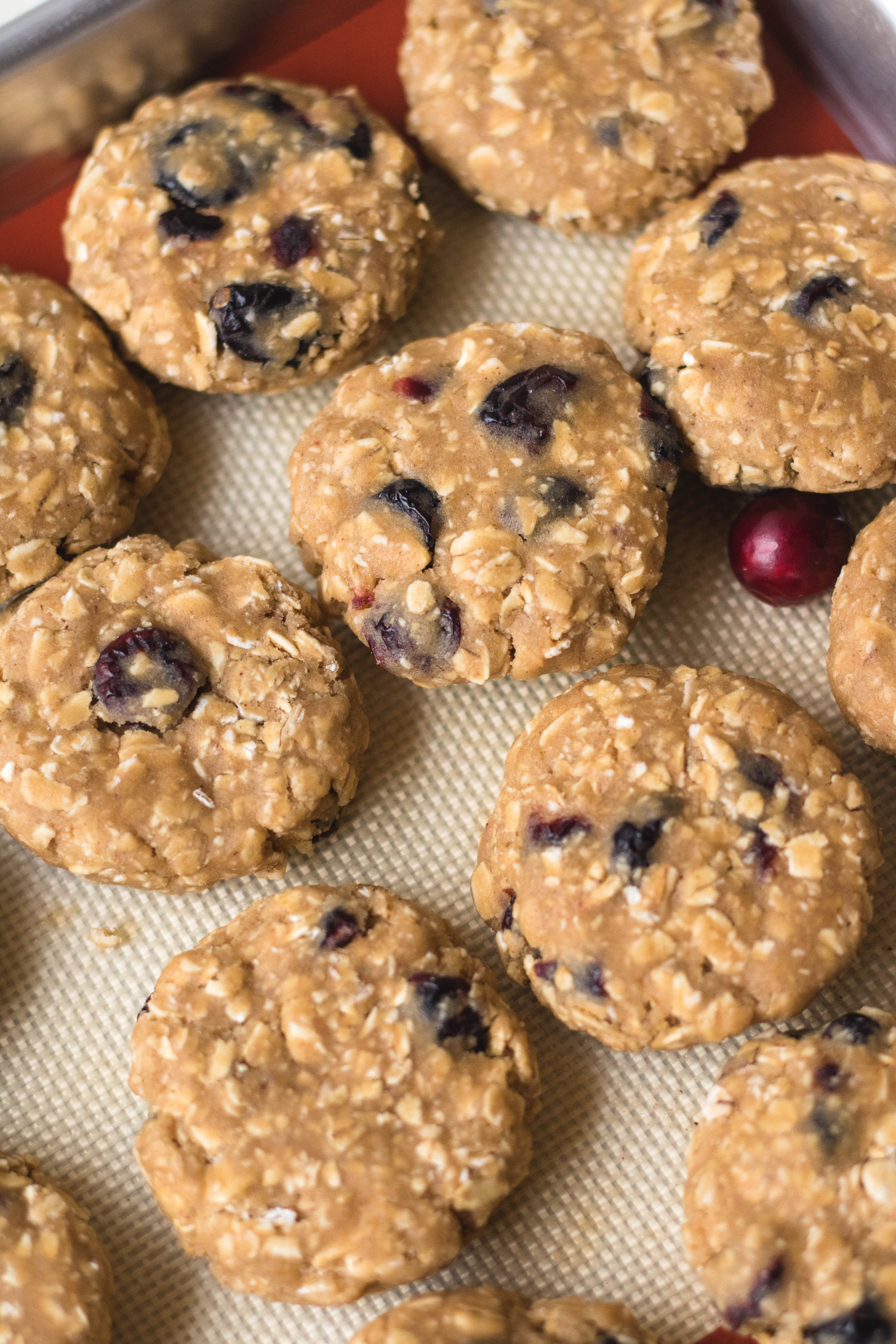 Raw oatmeal cranberry cookies on baking sheet before cooking