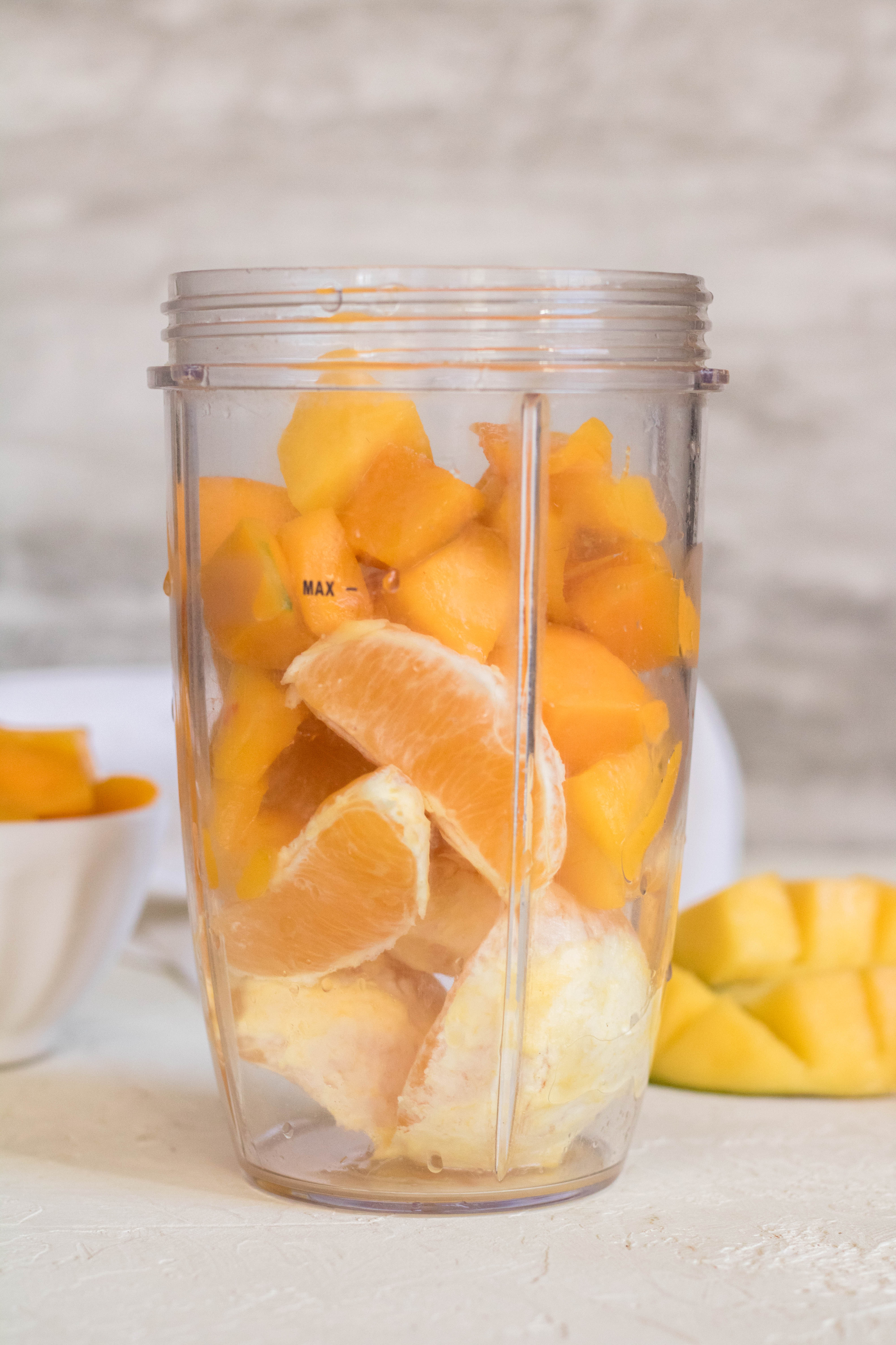 Ingredients of the mango orange smoothie in blender cup