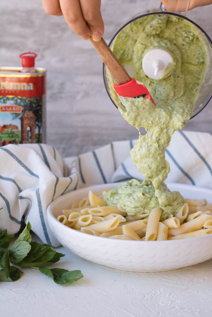 Pouring the avocado pasta sauce over the penne pasta