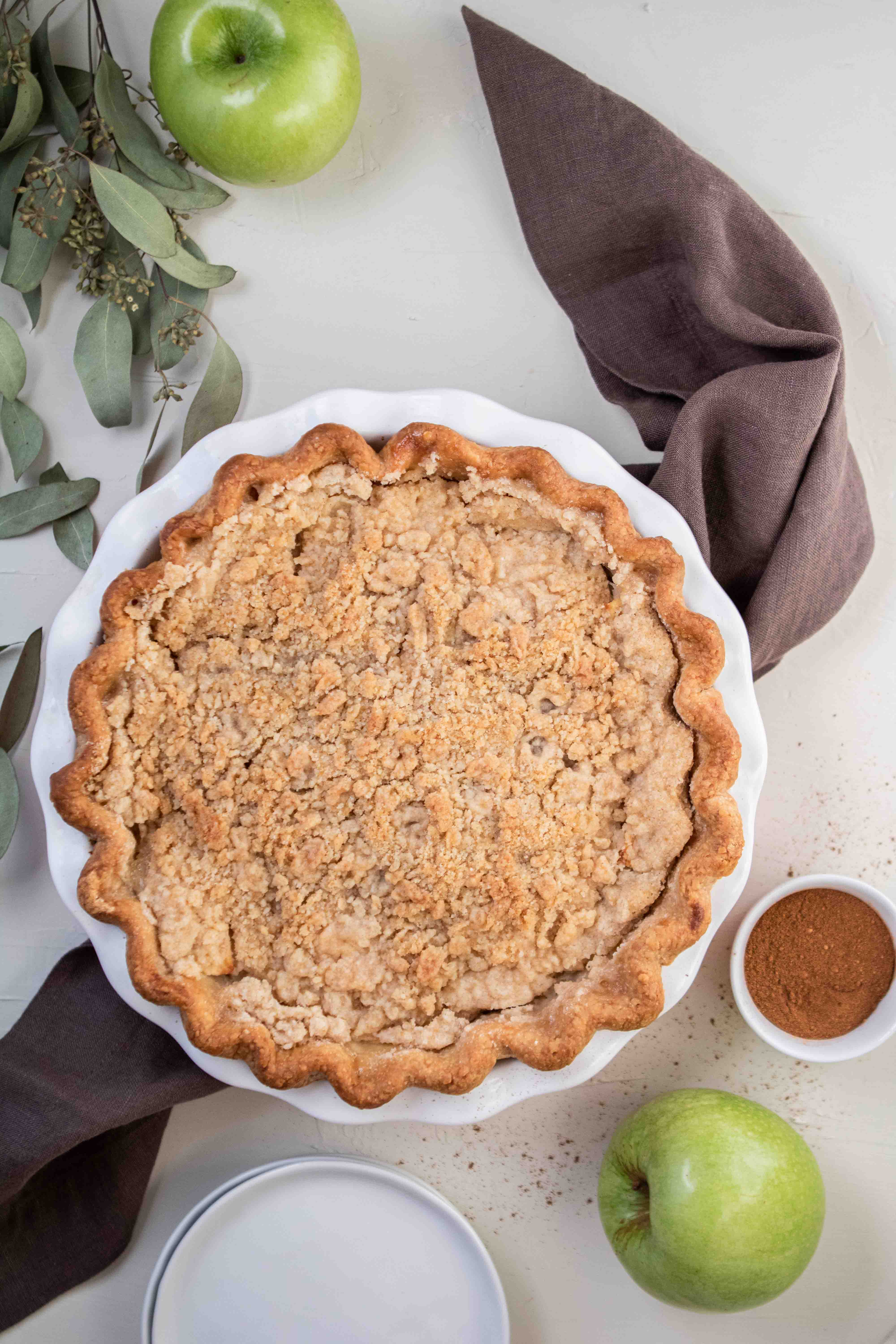 Overhead shot of dutch apple pie with apples on the side