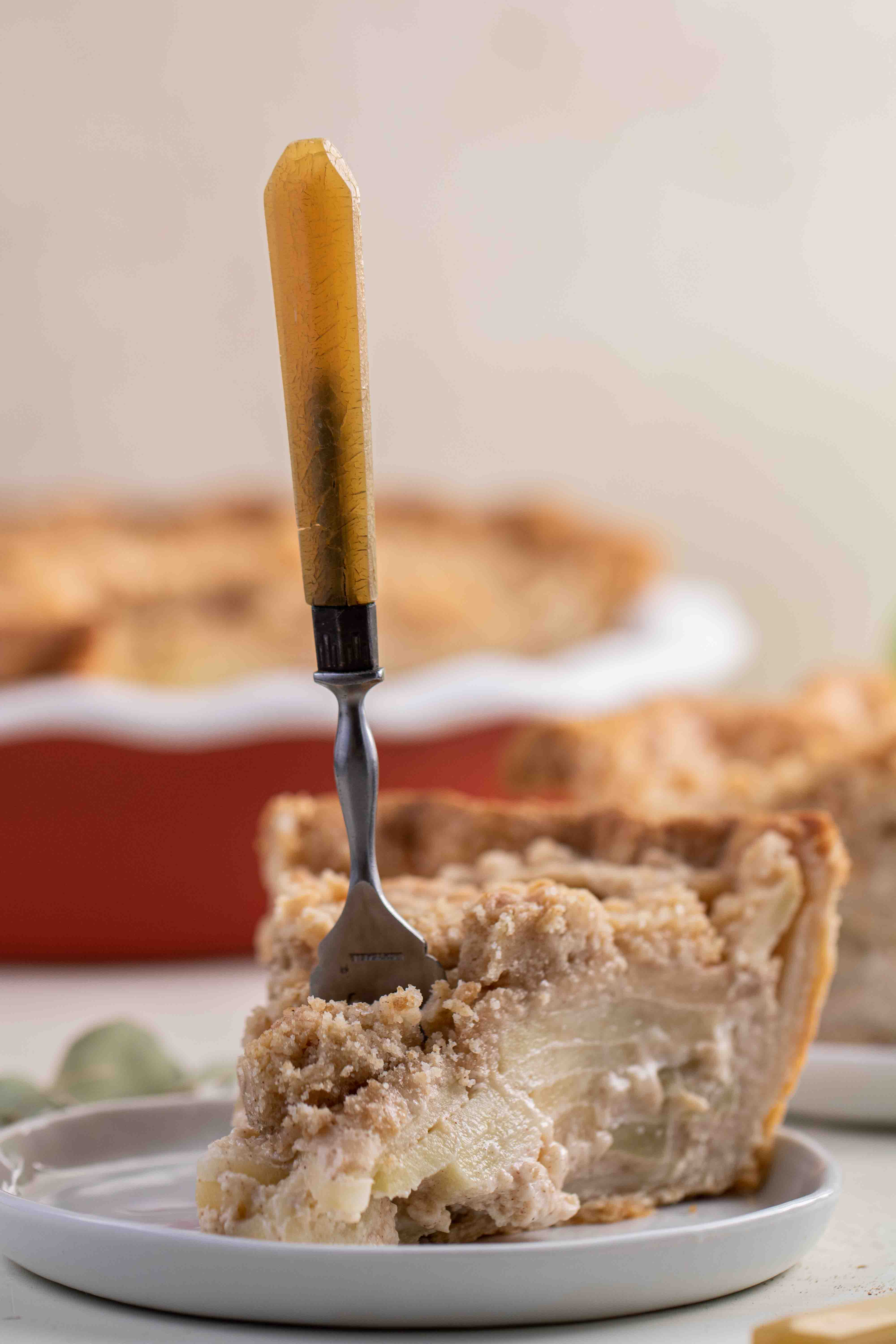 Apple pie slice with a fork inserted in the center