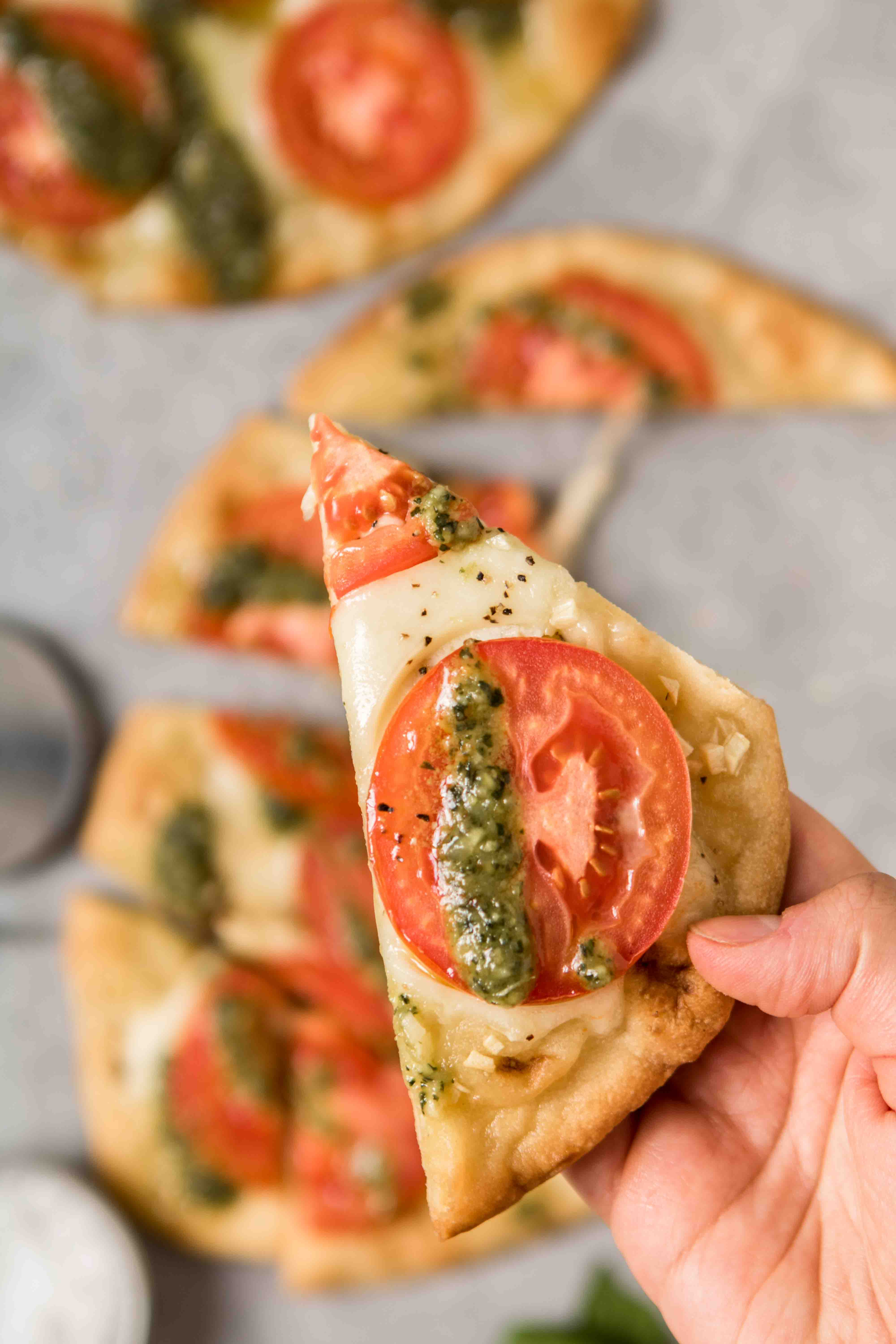 Hand holding a slice of naan bread pizza with pesto