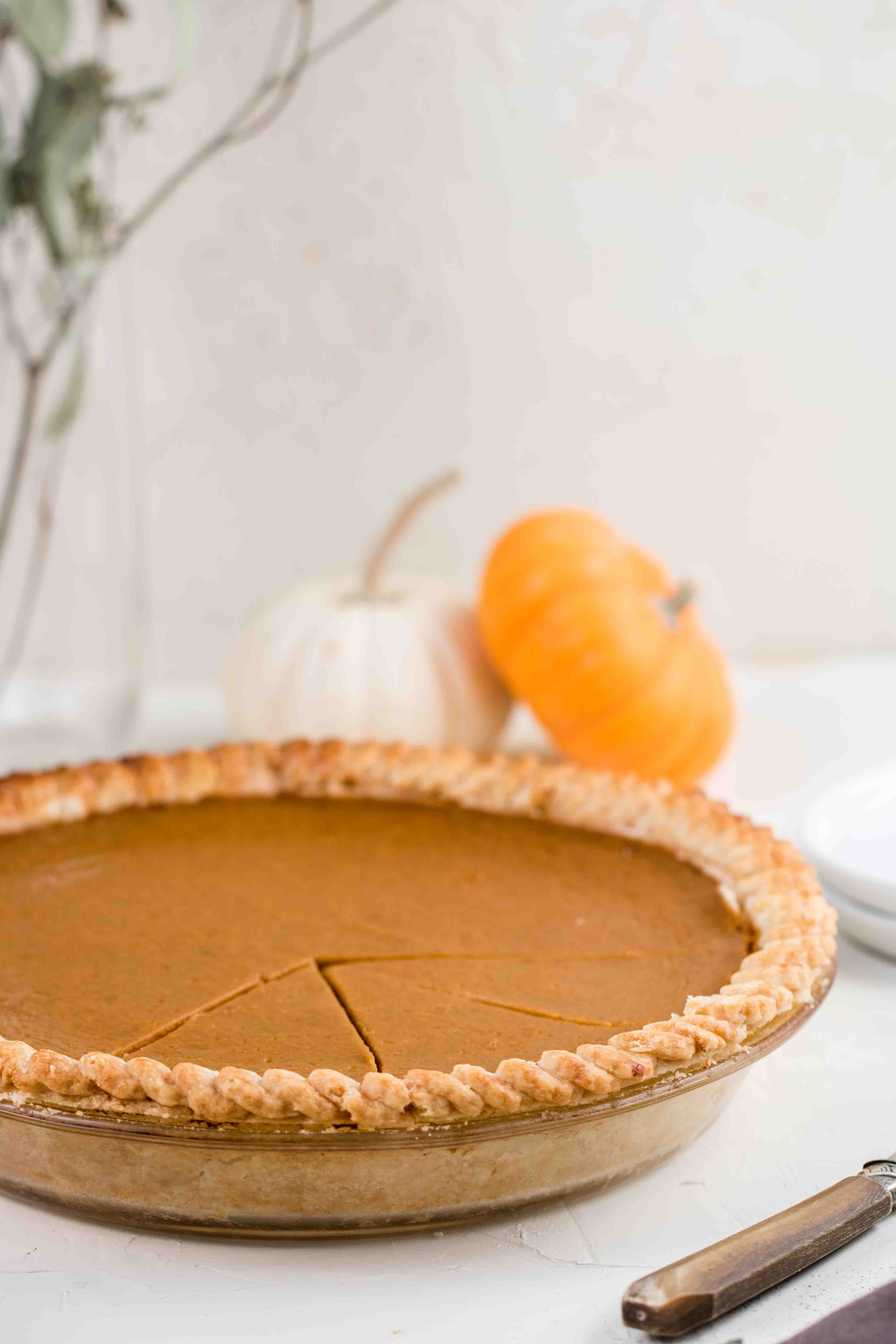 whole pumpkin pie with a few slices cut out and mini pumpkins in the background