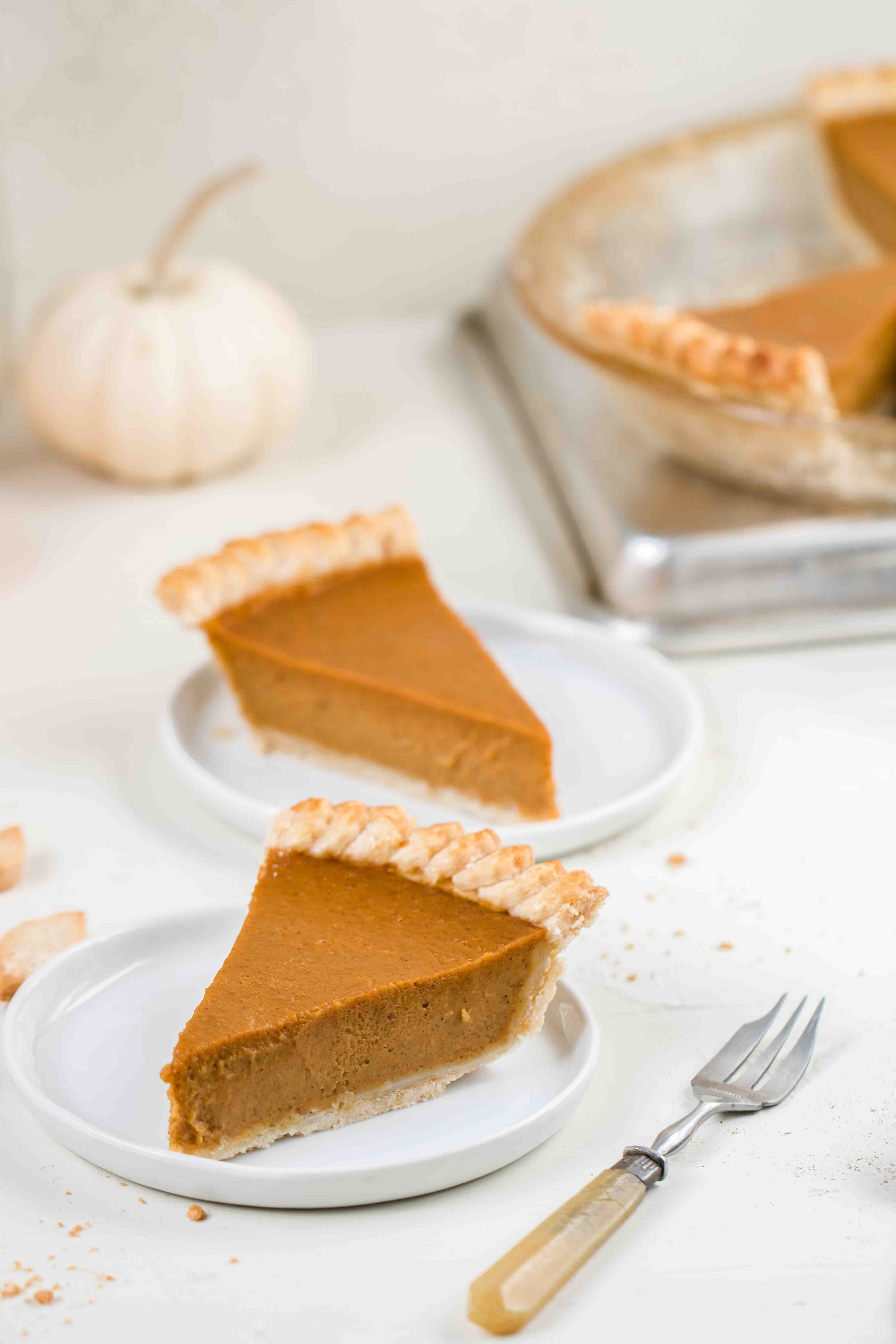 2 slices of pumpkin pie with a white pumpkin in the back