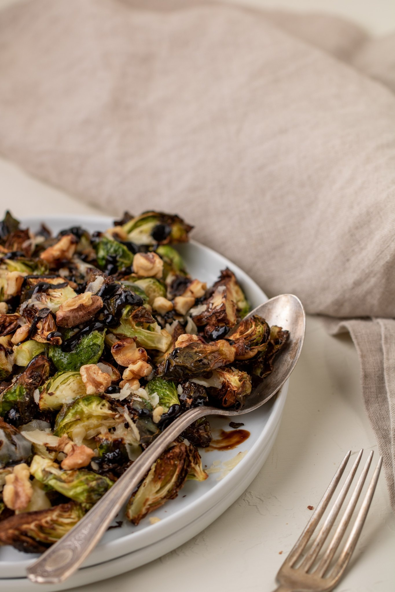 Plates stacked with brussel sprouts on top with balsamic glaze