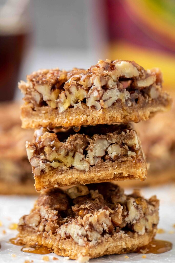 Stack of healthy pecan pie bars with maple drizzle