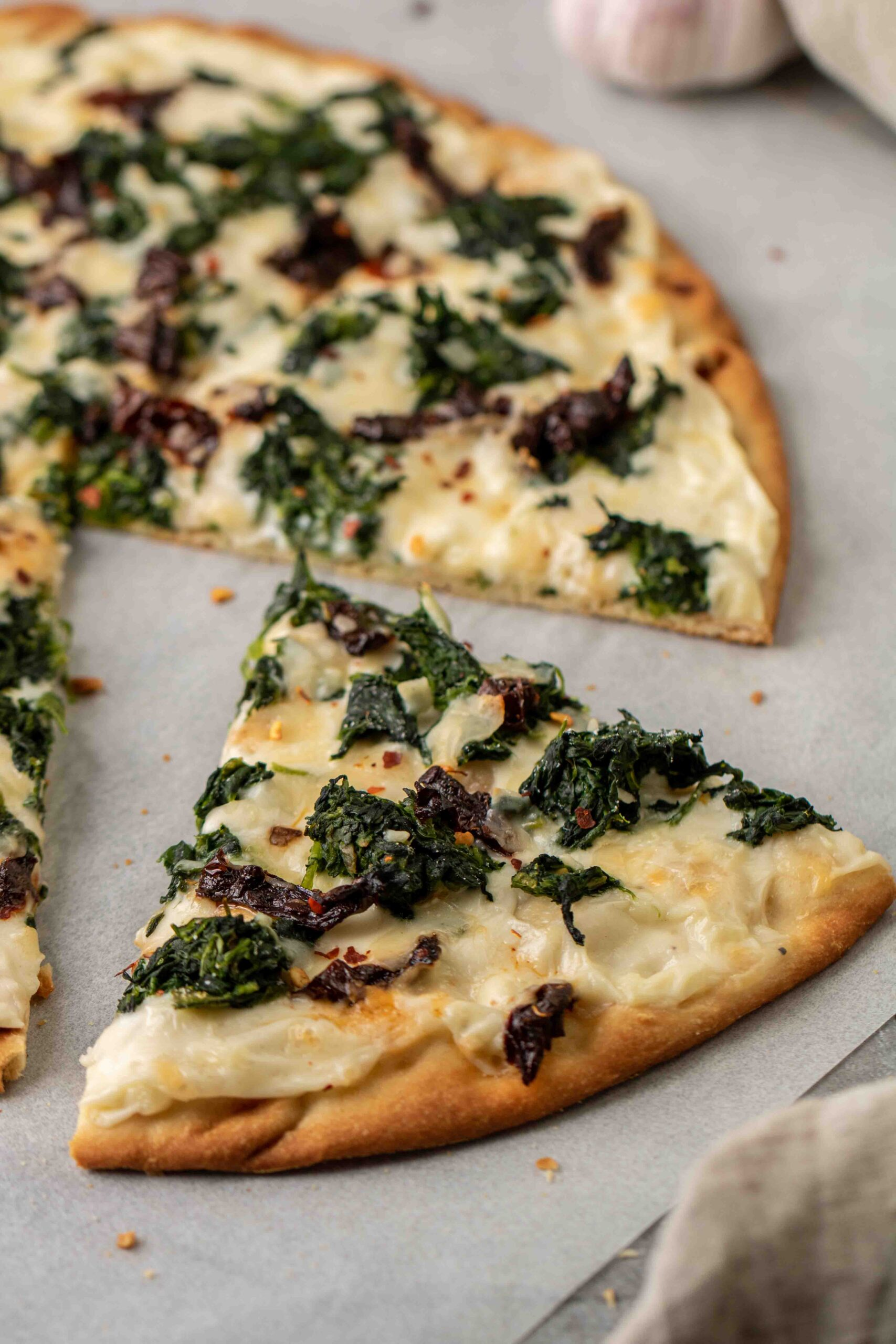Slice of spinach pizza with white sauce