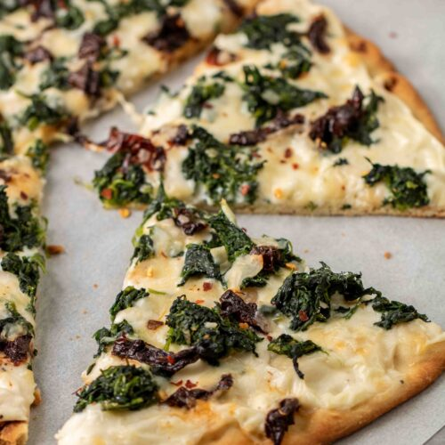 Baked slice of spinach pizza with white sauce