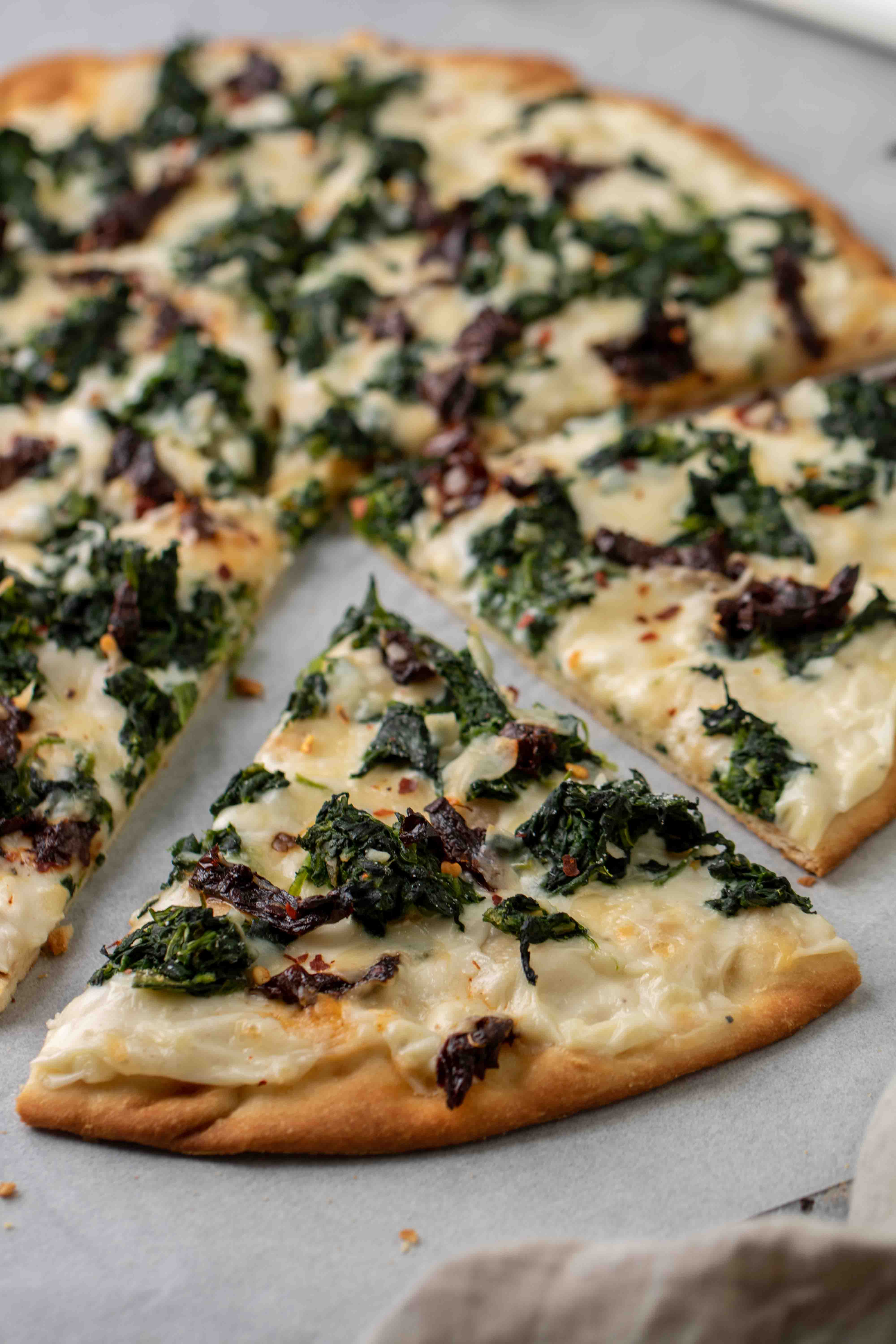 Pizza with white sauce, spinach and sun dried tomatoes