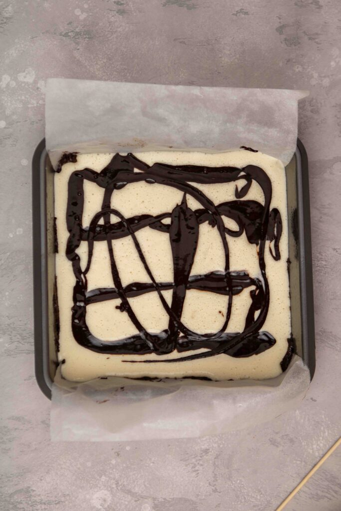 Pouring thinned out brownie batter over cream cheese layer