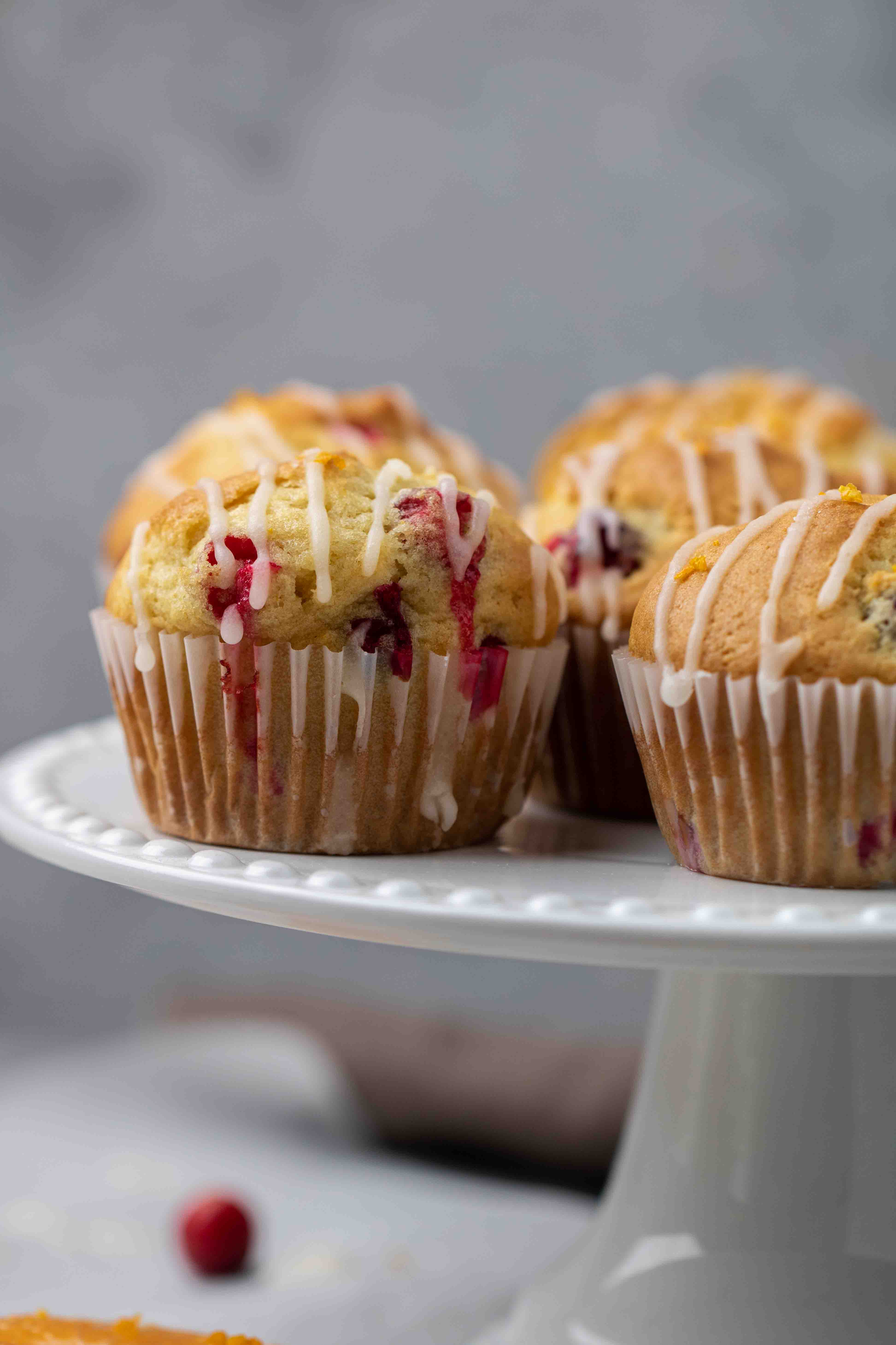 Bakery style cranberry orange muffins on a cake stand