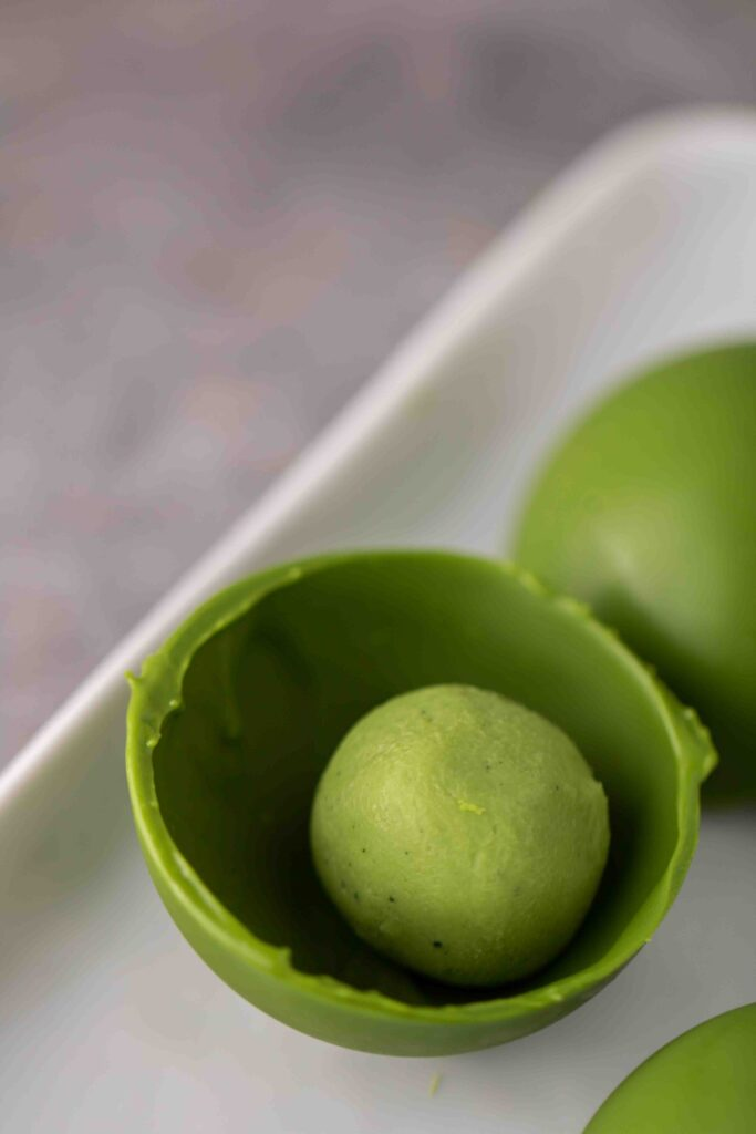 Half spheres of white chocolate matcha with matcha truffle inside