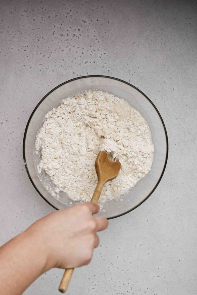 Mix the pizza dough with a wooden spatula