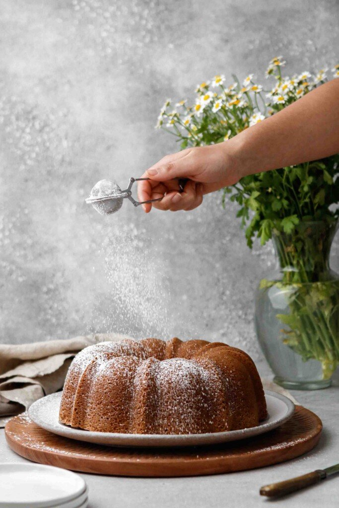 Dusting powdered sugar on cake