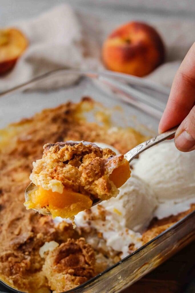 Spoon holding peach cobbler