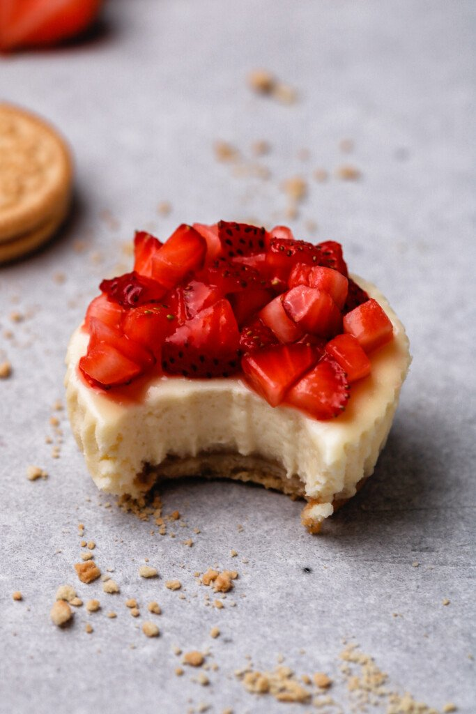 Close up of a strawberry cheesecake with a bite taken out of it