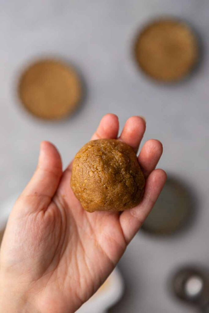 Hand holding cookie dough ball