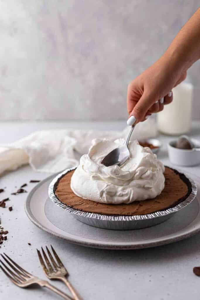 Decorating chocolate pie with heavy cream