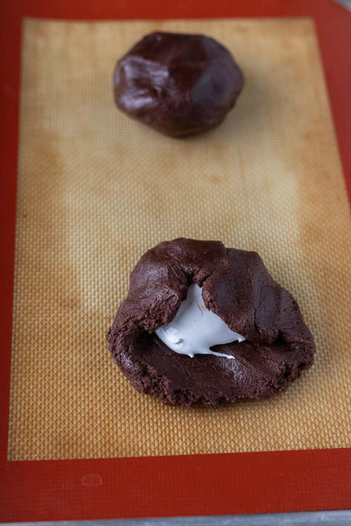 Filling a chocolate cookie with marshmallow fluff