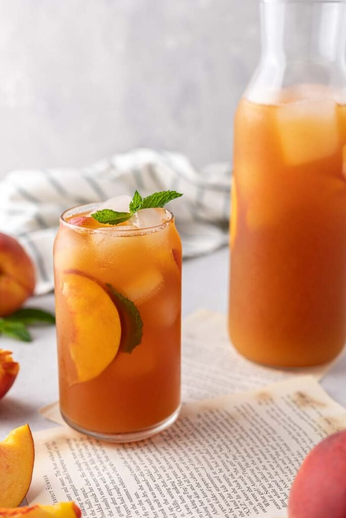 Ice cold peach tea next to pitcher
