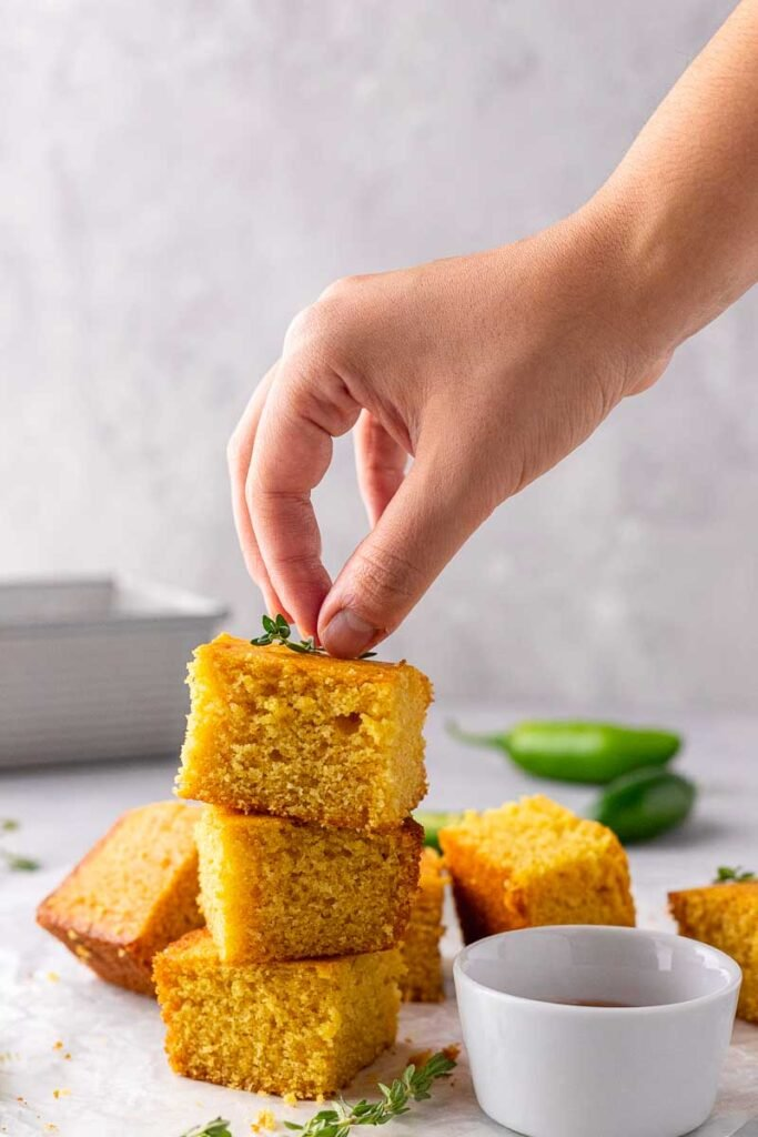 Hand placing thyme on cornbread stack